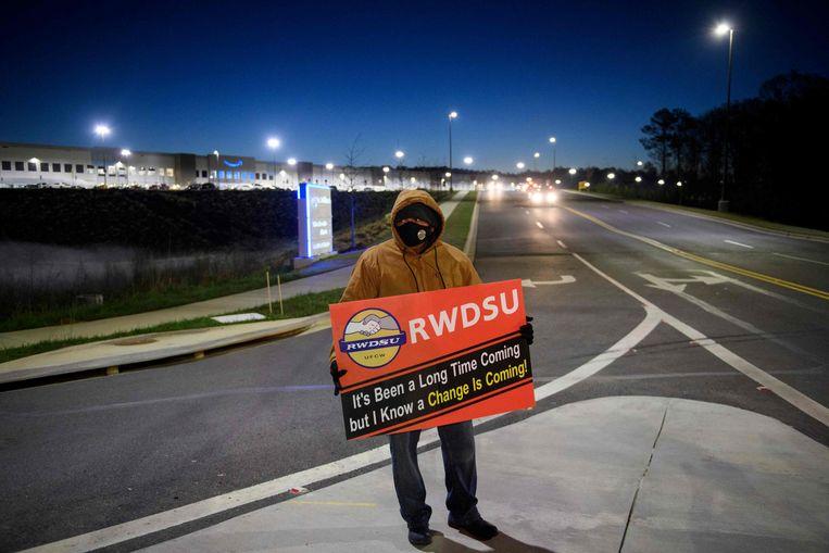 Een aanhanger van de vakbond staat voor zonsopgang bij het distributiecentrum van Amazon in Bessemer, Alabama. Te weinig werknemers stemden uiteindelijk voor het lidmaatschap van de vakbond. Beeld AFP