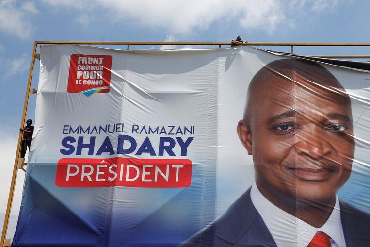 In totaal waren er 21 presidentskandidaten, onder wie Emmanuel Ramazani Shadary, de kandidaat van het huidige regime. Een banner met zijn gezicht erop wordt verwijderd in Kinshasa. Beeld REUTERS