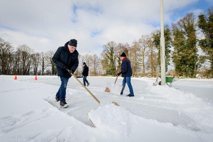 Toon Broshuis (rode kraag), Frans Broshuis (blauwe muts) en Hennie Averdijk (grijze muts) preparen de ijsbaan in Hengevelde.