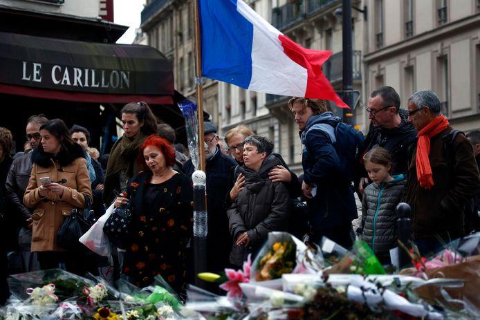 Archiefbeeld. Rouwende mensen op één van de plaatsen waar de terroristen toesloegen op 13 november 2015. In totaal vielen er 130 doden en raakten meer dan 350 mensen gewond.