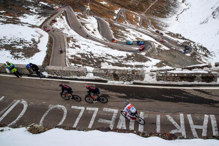 Jai Hindley (witte trui) krijgt zijn jasje niet aan op de Passo dello Stelvio in de Giro. Beeld Photo News
