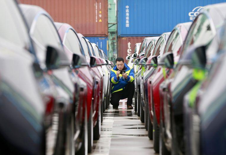 Een havenarbeider werkt tussen de elektrische auto's van Tesla die in een haven in Shanghai in China worden afgeleverd. Beeld AP