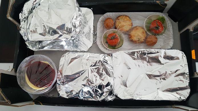 Zo krijgen we onze bestelling mee, netjes en warm in aluminiumbakjes en aluminiumfolie. De hapjes zitten in een kartonnen bordje met vershoudfolie, de desserts in plastic potjes.