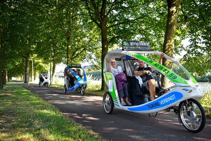 Een konvooi van drie fietstaxi's op weg langs het Maas-Waalkanaal.