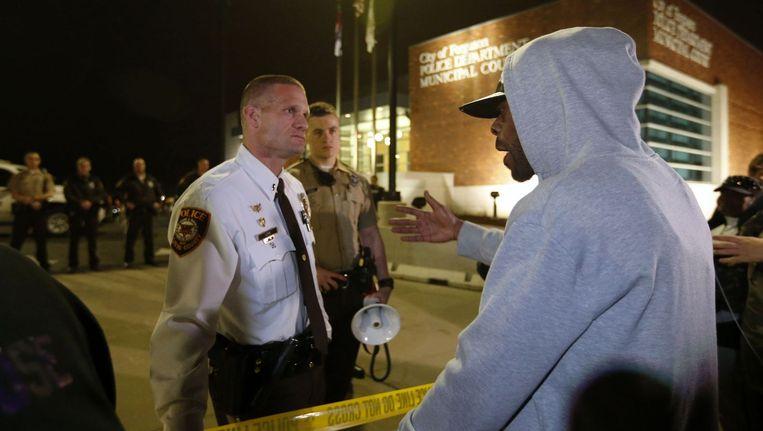 Een demonstrant praat met een politieagent Beeld reuters