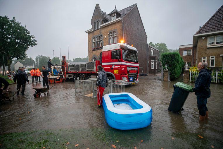 Zandzakken worden aangesleept in het waterschap De Dem in Hoensbroek. Beeld Harry Heuts