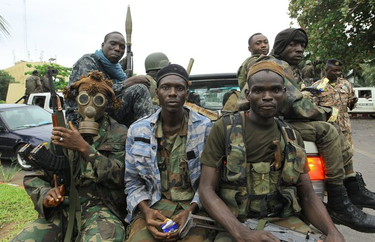 Pro-Ouattara fighters of the FRCI (Republican Force of Ivory Coast), one of them wearing a gas mask, prepare for the so-called