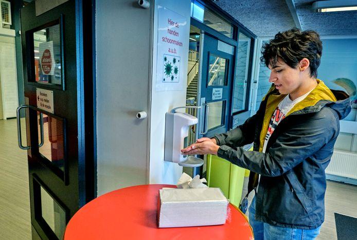Leerlingen op het Develstein College in Zwijndrecht moeten voordat ze de school binnengaan eerst de handen desinfecteren.