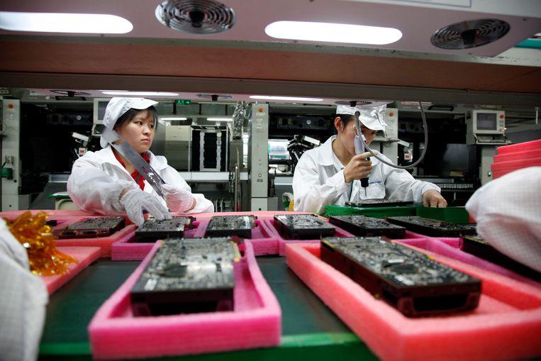 Chinese arbeiders aan het werk  in een fabriek van Foxconn in Shenzhen. Beeld Corbis via Getty Images