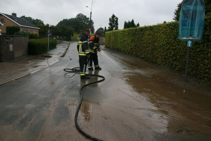 De brandweer van Torhout spoelt de modder weg.