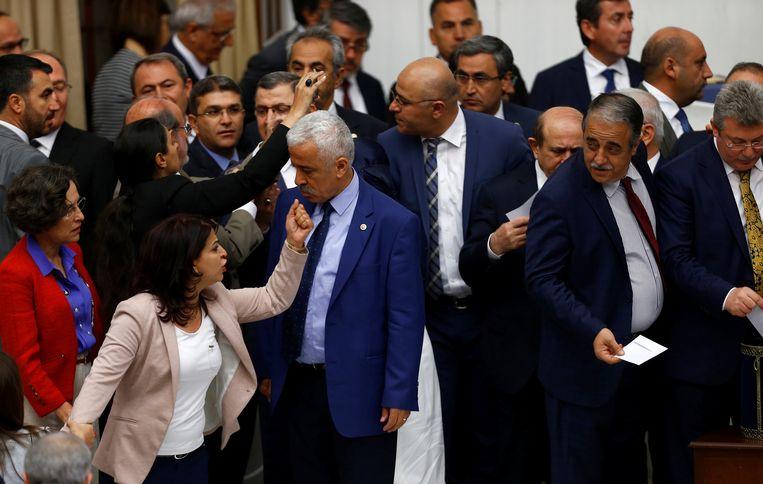 AK-parlementsleden (rechts) stemmen voor het wetsvoorstel dat Erdogan meer macht geeft, tot ongenoegen van de HDP-oppositie(links).