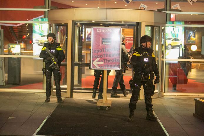 Zwaarbewapende agenten staan bij de ingang van het gebouw.