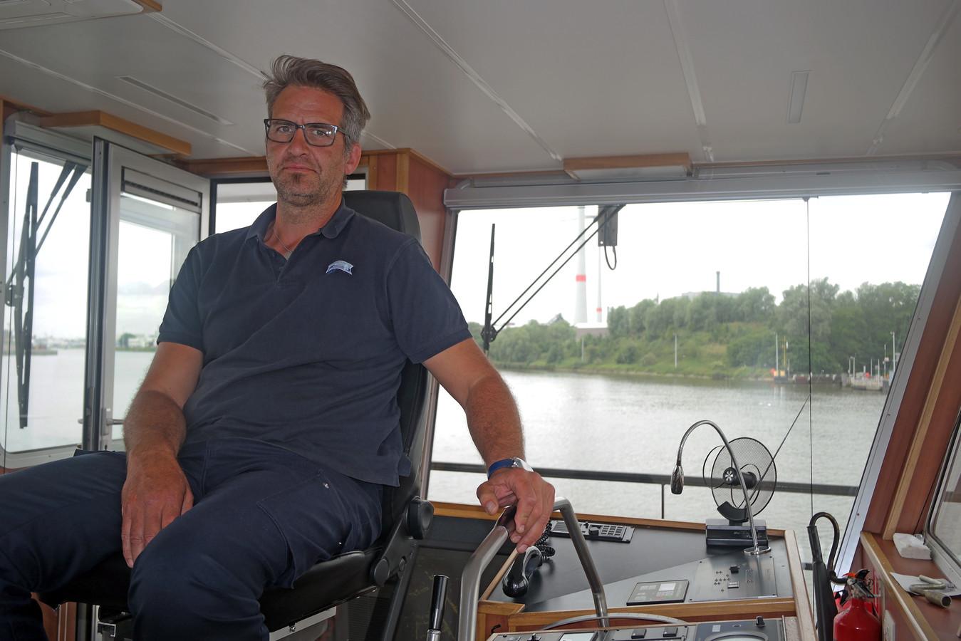 Kapitein Andy Hoste (49) op zijn veerboot, met zicht op Stora Enso.