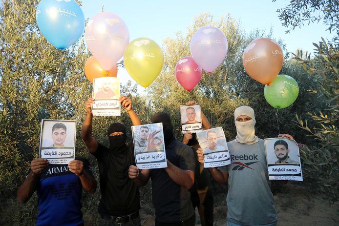 Gemaskerde Palestijnen maken zich klaar om aan de grens met Israel ballonnen op te laten met daaraan foto's van de zes Palestijnen die ontsnapten uit een Israëlische gevangenis.