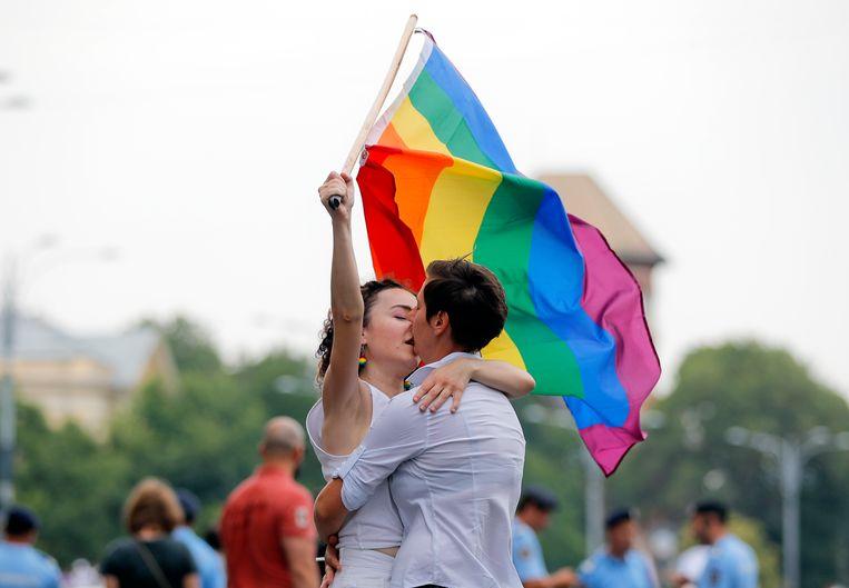 Twee vrouwen houden de regenboogvlag vast tijdens de Gay Pride in Boekarest. Beeld AP