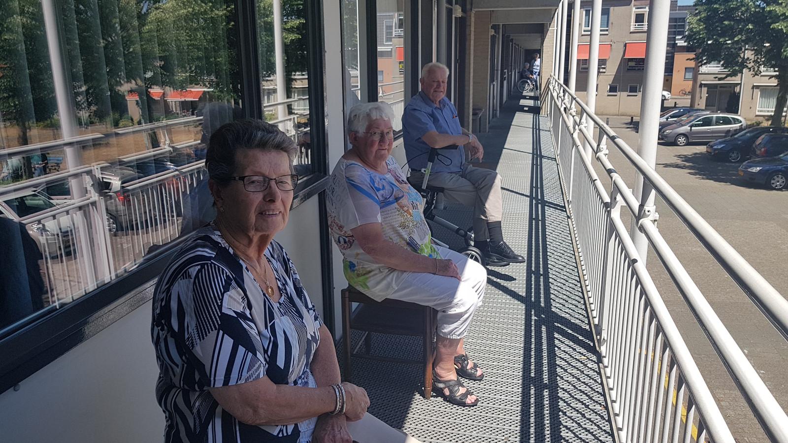 Marietje van Helvoirt, Joke en Theo van der Wijst (vlnr) rusten voor de deur uit op hun galerij.