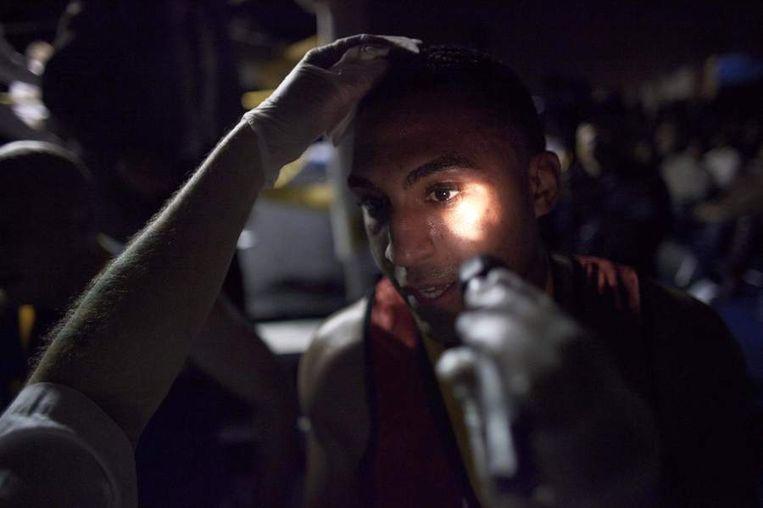 Een official controleert het aangezicht van een legerbokser op verwondingen na de wedstrijd. Beeld reuters