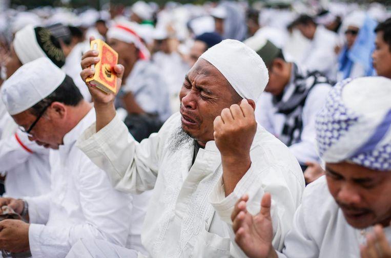 Een Indonesische moslim houdt een kopie van de Koran vast tijdens een bijeenkomst in Jakarta. Beeld null