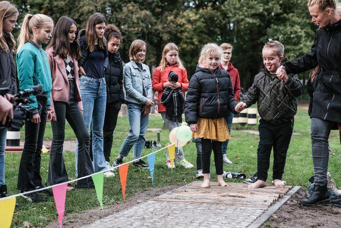 Luc (6) kan niet zien maar hij kan het blote voetenpad wel heel goed voelen in de nieuwe speeltuin voor álle kinderen in Doetinchem. Naast Luc staat zijn zus Fenna  die ook 6 jaar is. Kinderen van het jeugdparlement kijken toe.