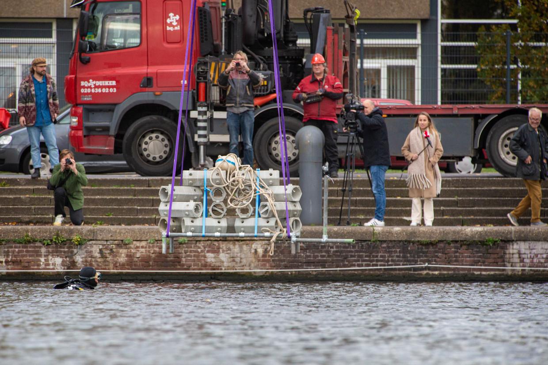 Een duiker begeleidde het kunstmatige rif gisteren naar de juiste positie op de bodem van het Oosterdok. Beeld Maarten Brante