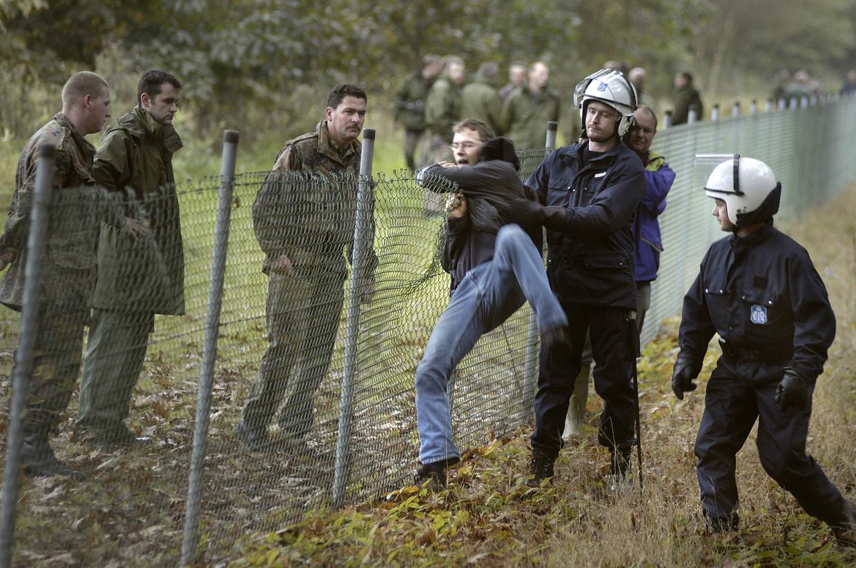 Een demonstrant klimt over de omheining van de militaire basis in Kleine Brogel tijdens een actie tegen kernwapens op 25 april 2004. Beeld Eric de Mildt