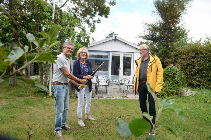 Peter Gelens en zijn vrouw Ria van Vlakhoven voor hun huisje op camping Duinrand, met Arno van Trigt (r) van de bewonersvereniging Duinrand Samen Sterk.
