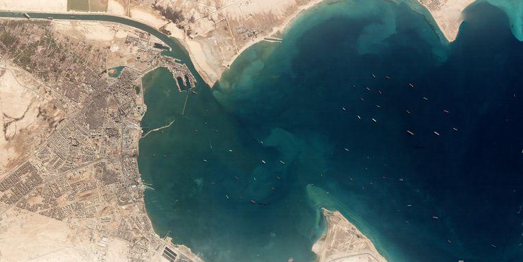 25 maart 2021. Tientallen containerschepen liggen werkloos te wachten tot de Ever Given, helemaal linksboven in het Suezkanaal, vlot wordt getrokken. Dat duurt een week. Beeld via REUTERS