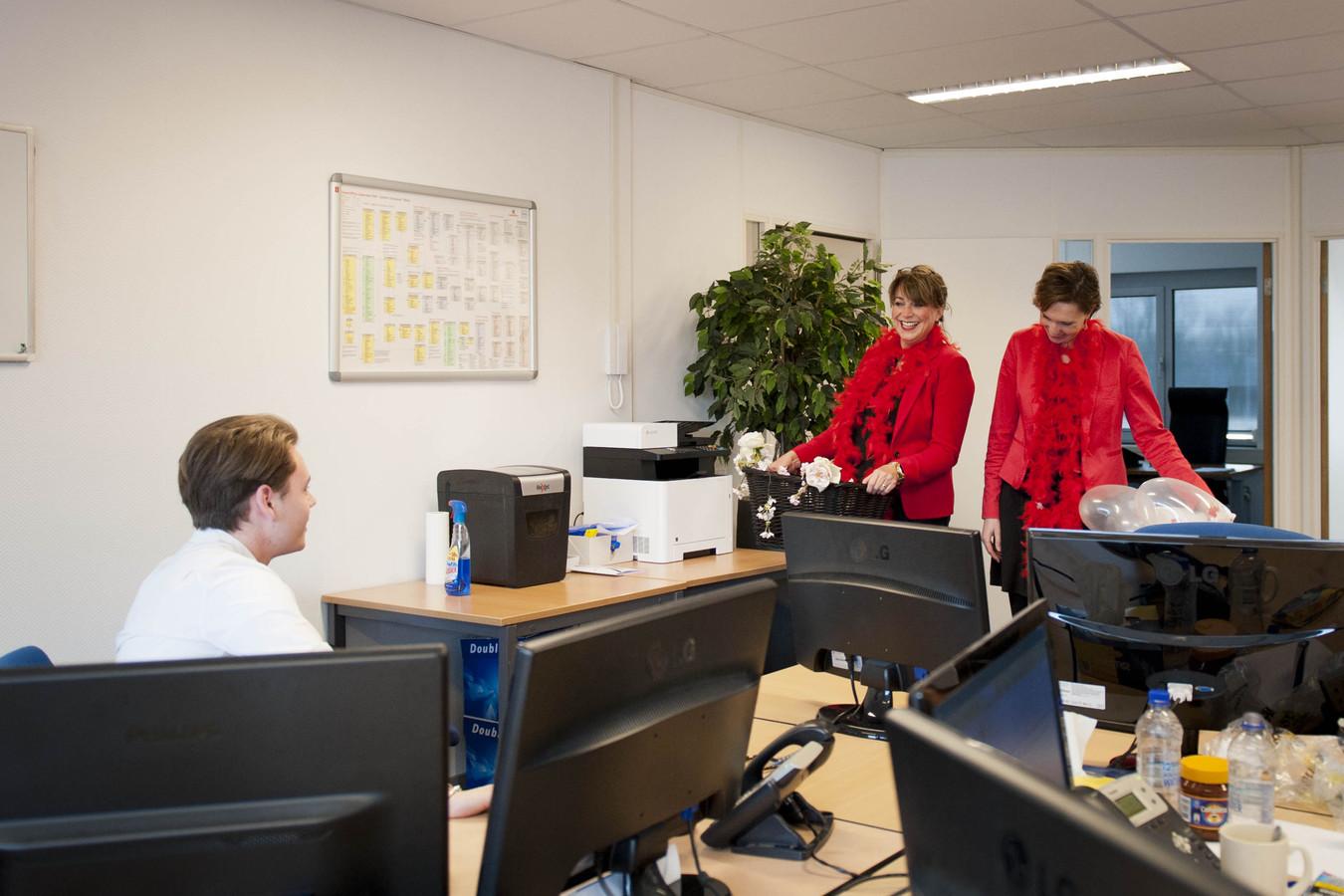 Pascal zit achter zijn bureau wanneer hij wordt verrast door Susan Nijhuis (links) en Lianne Jongsma.