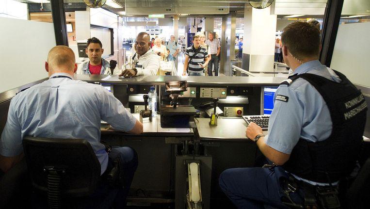 De marechaussee controleert passagiers op Schiphol. Beeld anp