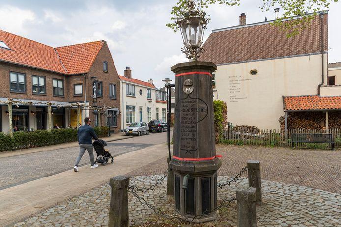 De gehavende Wilhelminapomp op het Kerkplein in Warnsveld, die met twee spanbanden overeind moet worden gehouden.