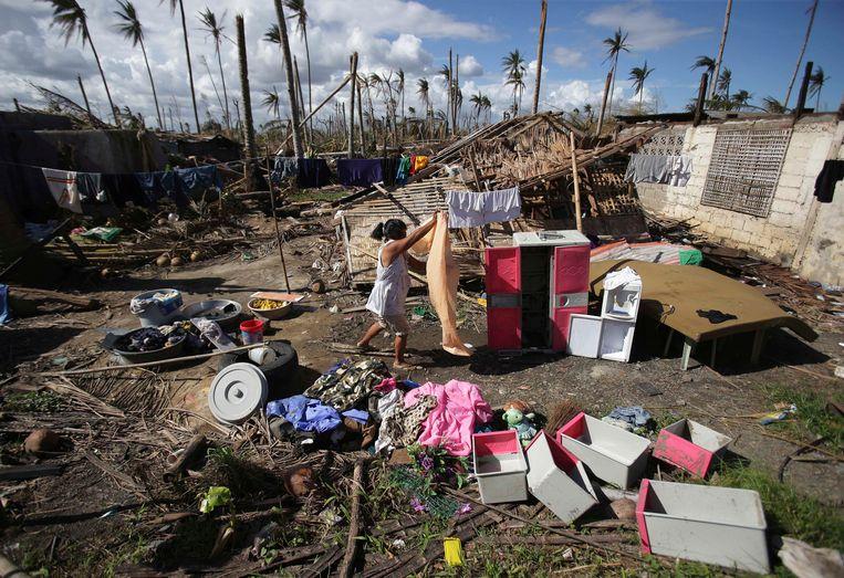 Een overlevende van de tyfoon wast haar kleren. Locatie: Tanauan, een dorp in de provincie Leyte. Beeld ap