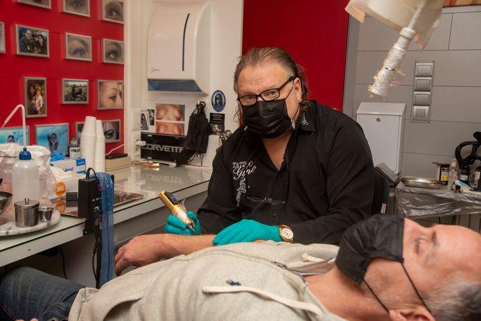 Gino aan het werk in zijn tattoo atelier.