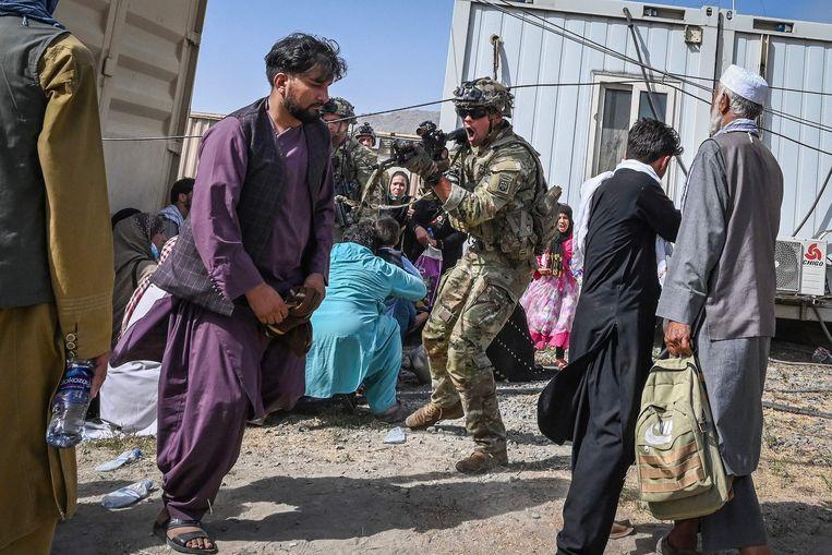 Een Amerikaanse militair richt zijn wapen op een Afghaanse man, maandag op het vliegveld van Kabul. Beeld Wakil Kohsar / AFP