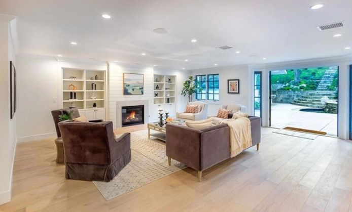 BGUK_1967331 - Los Angeles, CA  - Miley Cyrus buys new $4.5 million home in Hidden Hills, CA just two years after selling her previous home in the area. Back in 2015 Cyrus paid $5 million for a relaxed country spread in in LA's guard-gated and celeb-favored Hidden Hills enclave. According to reports the singer kept horses on the five acre farm before selling it in 2018 for $5 million. Now, after a brief stint in Malibu during which her home was destroyed in the Woolsey Fire in November 2018 that tore across Los Angeles and Ventura County, she's back in Hidden Hills where she recently dropped $4.95 million on a recently and comprehensively refurbished home. The deal closed quietly off-market but marketing materials from when the 1.25 acre estate was last on the open market at close to $5.1 million, describe the roughly 6,800 sq ft home as an East Coast traditional with six all en suite bedrooms and seven bathrooms. Built in the mid-1950s but reimagined for a modern, upscale lifestyle, the home now features gigantic multi-pane arched windows, wide-plank French oak floorboards and a wet bar in the family room that's jazzed up with cloudy Mercury glass panels. Just inside the front door there are adjacent formal living and dining rooms, the former with a vaulted ceiling and French doors to a terrace with serene views over the neighborhood. Configured around a huge, marble-topped island under a vaulted and skylight topped ceiling, the gourmet kitchen flows easily into the family room where a fireplace is faced in trendy shiplap and French doors lead to the outdoor living and entertaining areas. There's also a state-of-the-art screening room with eight black leather theater recliners and a 135-inch screen. The half-dozen bedrooms include two master suites, one on the main floor and a substantially larger one on the second level that offers a fireplace, balcony, walk-in closet and a vast bathroom replete with marble-lined steam shower and glam station. Outside, a lagoon-st