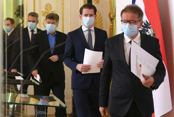 De bondskanselier en verschillende ministers, allemaal met een mondmasker, voor hun gezamenlijke persconferentie vandaag in Wenen over het versoepelen van de coronamaatregelen.