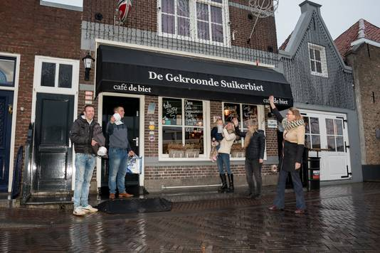 Gerrit van Loon (l) en Jim Stremme worden uitgezwaaid door hun partners en familie, voor ze zich vier dagen vrijwillig laten opsluiten in hun café De Biet in Zierikzee.