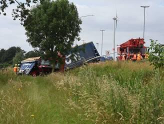 Vrachtwagen eindigt in gracht naast autosnelweg, chauffeur lichtgewond