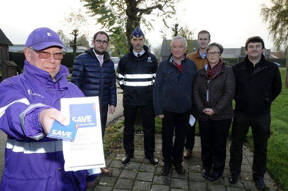 Een stadswacht met een flyer en sticker van het nieuwe netwerk. De initiatiefnemers kijken toe.
