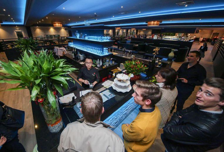 Zaakvoerder Huicong Hu van Daily World Kitchen bedient enkele klanten aan de kassa.