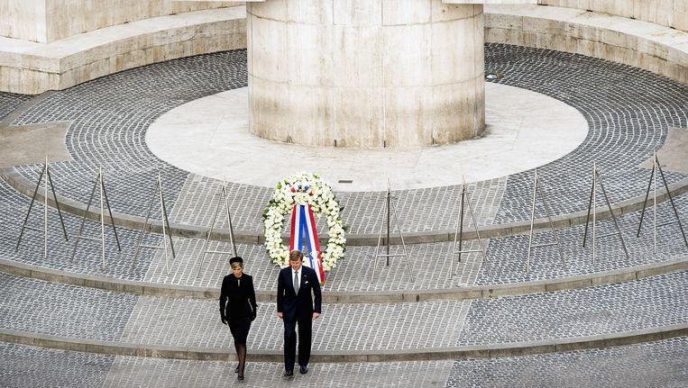 Koning Willem-Alexander en koningin Maxima leggen een krans bij het Monument op de Dam tijdens de nationale herdenking. Beeld anp