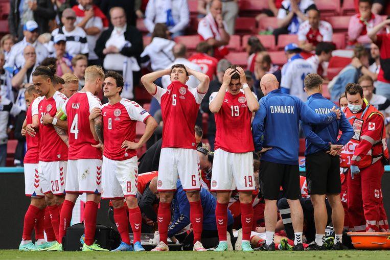 Deense spelers schermen hun ploegmaat Christian Eriksen af terwijl hij medische hulp krijgt nadat hij ineenzakte op het veld. Beeld AFP