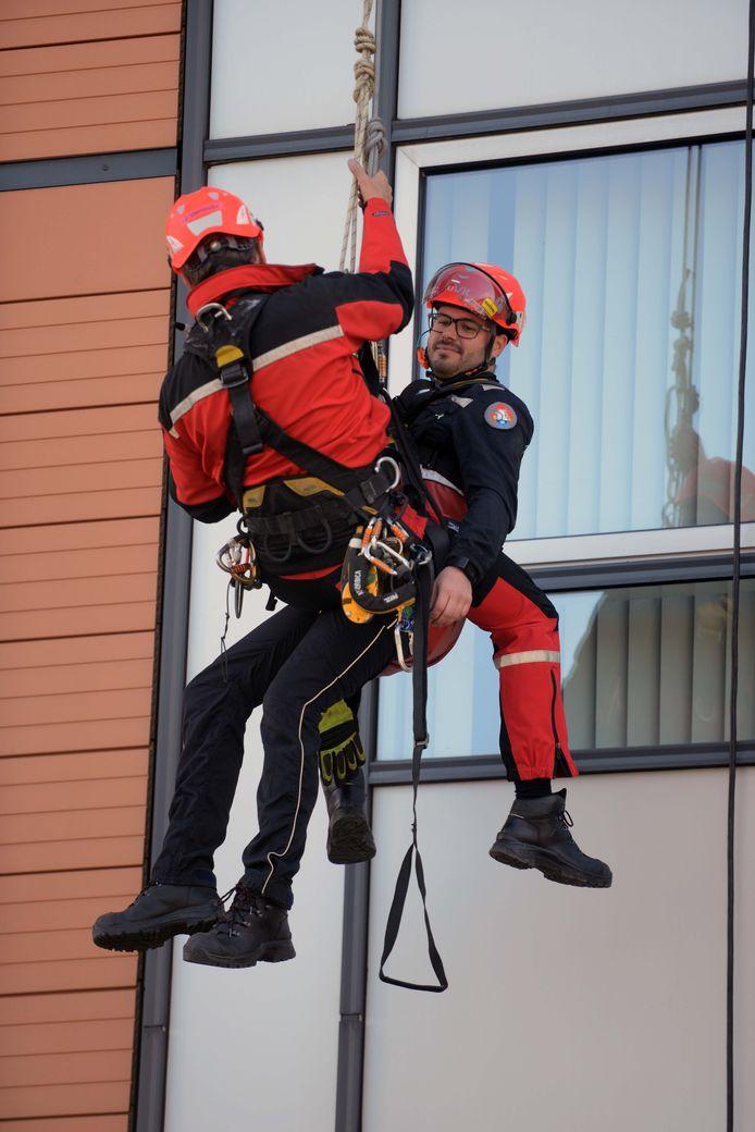 De Leuvense brandweer houdt een spectaculaire oefening in het abseilen aan de toren van het Sint-Maartensdal.