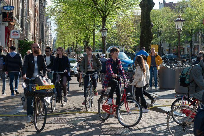 Fietsers en voetgangers langs de Amsterdamse grachten.