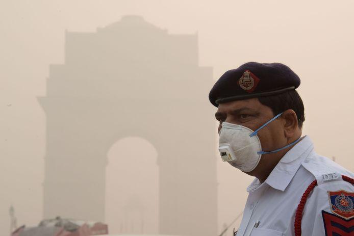 Een verkeersagent in de Indiase hoofdstad New Delhi draagt een mondmasker om de smog door uitlaatgassen te baas te kunnen.