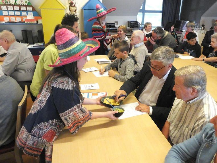 Minister Vandeurzen tussen bewoner Carlos en leerling Kasper. Na de spreekbeurt over Mexico kreeg de hele klas nog tortillachips met guacamole.