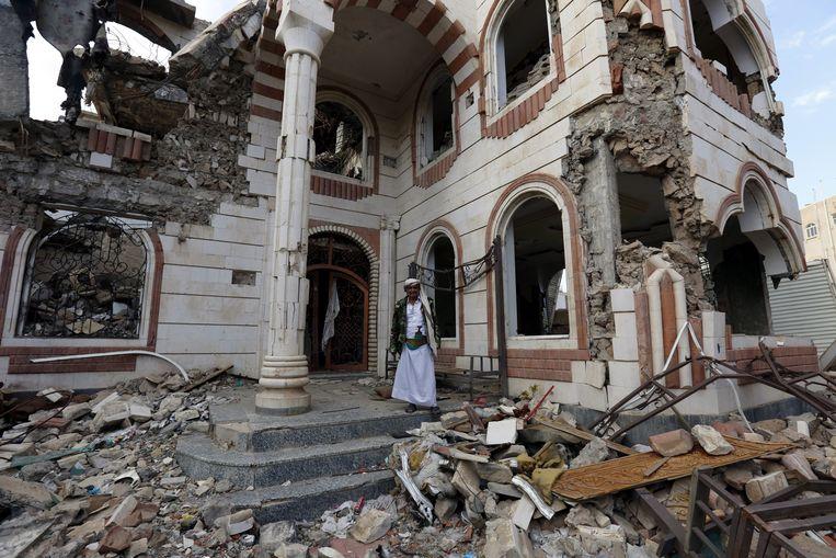 Een man staat tussen wat overblijft van een huis in de Jemenitische hoofdstad Sanaa, na een aanval van de door Saudi-Arabië geleide coalitie. Beeld EPA