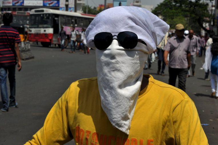 Een man probeert zijn gezicht te beschermen tegen de zon. Beeld anp