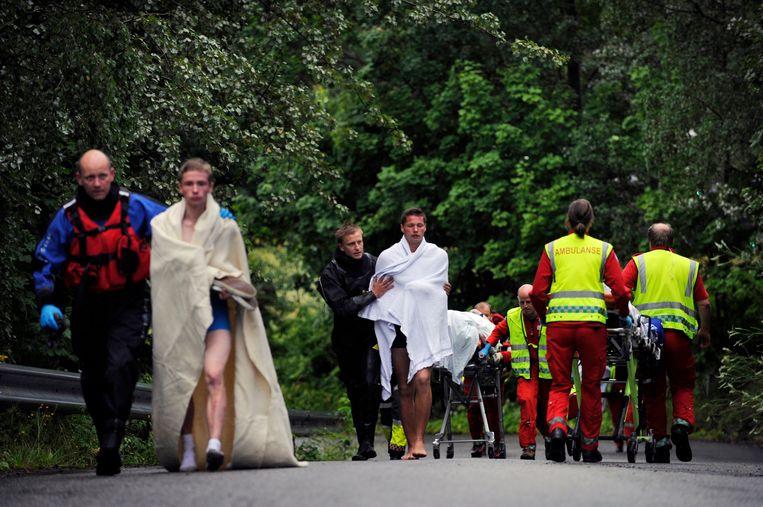 Hulpverleners helpen overlevenden na de moordaanslagen. Beeld AP