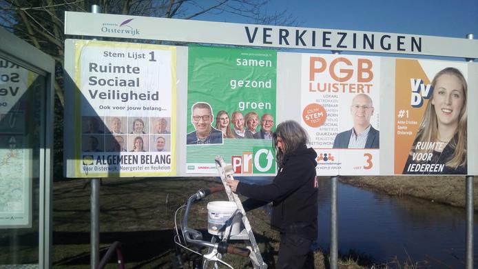 Guy de Kort plakt een nieuw affiche op het verkiezingsbord aan de Reusel in Moergestel.