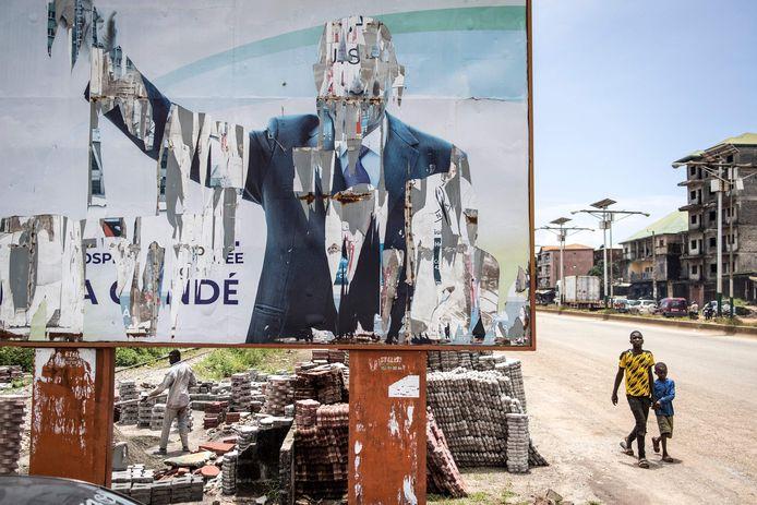 Een billboard met een half afgescheurde poster van de oud-president van Guinee Alpha Condé.